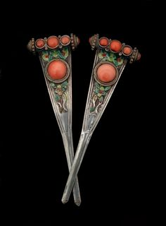 Two silver hairpins illustrated are decorated with coral beads and coloured enamel. These hairpins were once part of the lavish and complex head ornamentation worn by Mongolian women when dressed in traditional costume; late 19th or early 20th century.