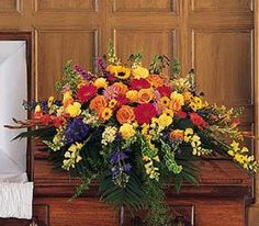 Funeral casket spray with multi-color flowers.
