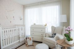Chic gender neutral nursery features accent wall clad in beige floral wallpaper lined with a Pottery Barn Kids Kendall Fixed Gate Crib dressed in white and beige giraffe crib bedding and a beige crib skirt with white ribbon trim adorned with a sheep mobile beside an Ikea Hemnes 3 Drawer Chest topped with a changing pad and rocking sheep placed in front of a window dressed in white sheers.