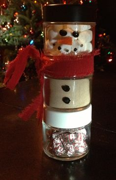 My version of the Snowman Craft.  Jars from dollarama,orange felt nose glue gunned on,fabric paint for black dots, cut up cloth for scarf,marshmallows,hot chocolate,and candy cane kisses.  Works great as only 2 jars too omitting the bottom jar.