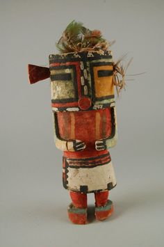 Malo kachina tihu, Hopi. Colton 130 (table 13). [jcx]. Case mask, tube mouth, rectangular eyes, nose a vertical line : a checker board for Malo. Blossom in place of one ear, tuft of hair on other, with feathers. Brooklyn Museum