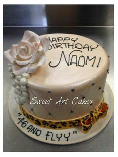 Smooth ivory buttercream, gumpaste flower, handpainted rolled fondant ribbon and bow, piped pearls.