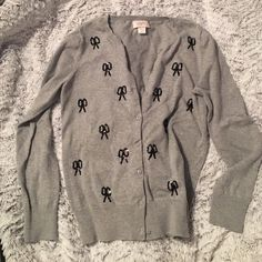 LOFT Gray Sweater w/ Bows Gray LOFT cardigan with black sequence bows. Sweater was only worn one time and is in great condition. One very small and faint stain inside back (you can see in photos). Does not show through to back, cannot see stain when wearing sweater!! LOFT Sweaters Cardigans