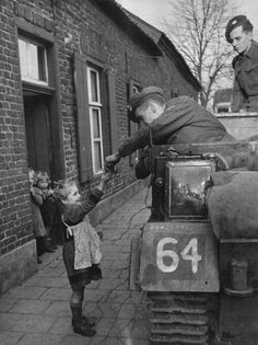 Allied servicemen stop to hand out sweets to Dutch children during the Allied liberation of the Netherlands, summer 1944.