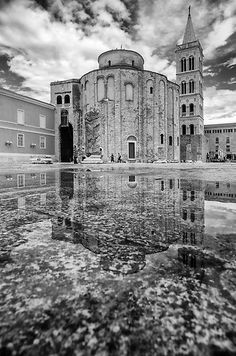 Church of St. Donat, with bell tower of St. Anastasia cathedral in reflection after the rain. City of Zadar, Croatia