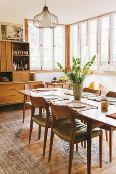 How to create the new bohemian look at home: The eat-in kitchen in this 1920s cabin is warm, bright and inviting. Mid century furnishings sit on a faded Persian rug giving the space a rustic, handmade feel.