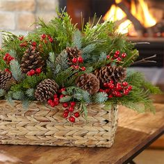 Christmas arrangement of greenery, pinecones and red berries in a basket.