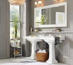 A chandelier in the bathroom? Why not! The gray walls in this classic bathroom make it look extra chic.