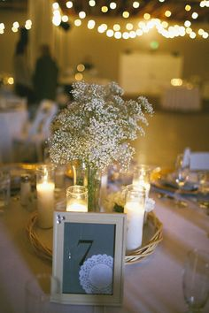 Simple centerpieces of candles and baby's breath via The Wedding Chicks