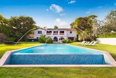 This Miami home has white stucco walls, spanish tile roofing, a linear infinity pool, a vibrant green lawn, fountain features, and lounge chairs in the expansive lawn.