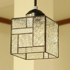 サイズ:ガラス本体 11.8×11.8×高さ11.5cm    コードの長さ 50cm    天井からガラスのすそまでの長さ 約70cm技法:ステンドグラス素材:ガラス、はんだ電球:40W電球をおつけします(口金サイズ:E17)    (LED電球も使用可能ですが、この場合は調光タイプのシーリングには使えません)総重量:約710gいろいろなタイプのクリアガラスをパッチワークのように組みあわせました。シンプルで涼しげな印象のランプです。2面はパッチワーク風に組み合わせ、2面は凹凸のあるクリアガラスです。※引掛シーリングに吊下げてご使用いただくペンダントライトです。スイッチはついていません。 ※ステンドグラスの「ふちどり」部分は黒色が一般的ですが、本品は濃茶色に加工し、アンティーク風に色むらを出しました。※型ガラスの模様のでかたは、1点ごとに多少異なります。