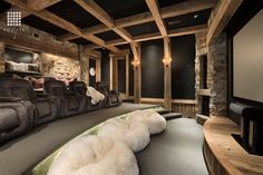 This three-tiered rustic home theatre has velvet recliners, a large bench seat at the top, and a row of soft, furry bag chairs on the lowest tier. What do you think of the stone and wood accents in this room? Source: http://www.zillow.com/digs/Home-Stratosphere-boards/Random-Rooms-I-Like/