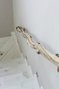 This beautiful and unique driftwood stair rail and the bleached wood floor stairs adds such a beachy feel.