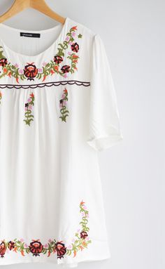 White one size fits all tunic with floral embroidery and sleeves that hit above the elbow. Fits loose. Absolutely beautiful design and just screams spring/summe