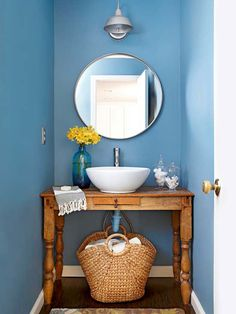 Bold color and rustic-chic elements give a powder room a cool and collected vibe. A favorite desk-turned-vanity fits the nook in this bathroom perfectly, saving big money. The rich espresso floors and warm wood vanity offset the walls cool color.