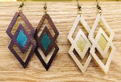 Handmade faux leather earrings with two-tone colors and geometric cutouts. Faux leather comes in deep metallic colors that shimmer in direct light. Comes in beige / gold and chocolate brown/ peacock green. These are extremely lightweight and have a ton of movement. Comfortable and fun for any age! *Variation in colors seen in photos is due to light shining on metallic surface. Earring pairs are made from the same cut of faux leather and will match in color.