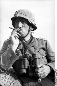"""An Oberleutnant of the """"Großdeutschland"""" Division smokes a cigar as he looks off into the Romanian counrtyside. Area of Târgu Frumos, Romania, between 2 and 8 May 1944. He has received the Eisernes Kreuz 2. Klasse and Medaille """"Winterschlacht im Osten 1941/42""""."""