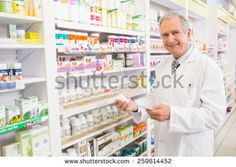 Smiling senior pharmacist holding medicine and prescription in the pharmacy