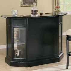 This sophisticated contemporary bar unit will add a sleek look to your entertainment room. The half-octagon shape is bold in a rich dark wood finish. Glass panels will show off your favorite bottles, with four shelves behind the panels for sufficient storage. The back of this bar also features a generous work surface, hanging stemware racks, a drawer, and glass doors with wine bottle holders and shelves inside to help keep you organized. Simple silver tone contemporary metal hardware…