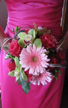 A bridesmaid's bouquet of ours that features hot pink roses, light pink gerbera daisies, and green cymbidium orchids with green hypericum berries and silver bear grass accents.