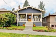 Small simple blue grey craftsman style house with white porch. Stock Photo - 12760946