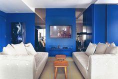 Dois sofás menores, colocados na vertical na sala de estar, possibilitam receber mais gente. O layout comum seria usar apenas um sofá de frente para a TV. Confira mais dicas no blog!