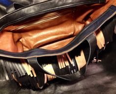 Bag made of black leather and decorated with straps of innertubes.
