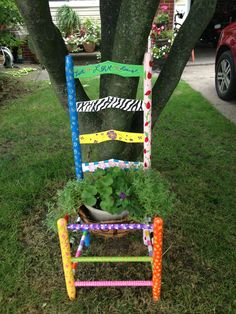 An old wooden chair repurposed to an outside plant stand