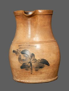 "Sold For $ 450 One-Gallon Stoneware Pitcher with Cobalt Floral Decoration, Stamped ""COWDEN & WILCOX / HARRISBURG, PA,"" circa 1865, ovoid-bodied pitcher with pronounced foot, tooled midsection, and tall flaring collar, decorated with a brushed tulip motif. Professional restoration to tip of spout, rim chips, and a 2 1/4"" hairline from rim on reverse. Two minor chips to rim and a minor chip to shoulder molding on side of pitcher. Several small base chips."