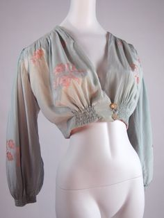 Gorgeous powder blue and pink silk charmeuse bed jacket from the 1940s.  The jacket has padded shoulders as well as soft padded bishop sleeves, floral applique', and is reversible.  Hand ruched shoulders and bodice.  Closes with two large oval mother of pearl buttons.