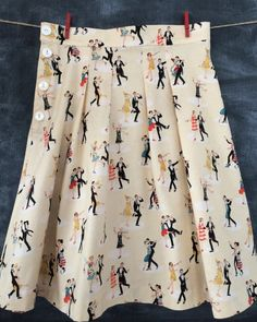 Super cute and trendy lady's cotton pleated skirt in Size 6 - 8.  The fabric print shows Flapper couples dancing the Charleston on a beige background.  The skirt has a true waistband (not gathered with elastic) and a 4 shell button side closure.  Four pleats in front and in back make for a nice little twirl skirt that all of your BFFs will envy.   Own this one of a kind skirt for only $40.   Baby Suzanna Johanna