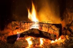 Flames burning in the fireplace spreading warm light around. Stock Photo