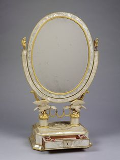 Toilet mirror. Place of origin:Vienna (city) (made)  Paris (possibly, sold) Date:ca. 1821 (made) Artist/Maker:Schmid, Karl (possibly, maker) Materials and Techniques:Oak, veneered in mother-of-pearl, with gilt-bronze mounts; a painting in gouache