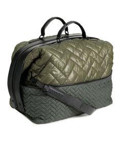 STUDIO COLLECTION. En quiltad, vadderad weekendbag i nylon. Väskan har dubbla handtag och avtagbar axelrem i läder. Grov tvåvägsdragkedja upptill. Gevärsknappar i sidan som du kan reglera väskans volym med. Ett ytterfack och tre innerfack, varav ett med dragkedja. Fyrkantiga nitar i botten. Fodrad. Storlek 28x40x49 cm. 2 499:-