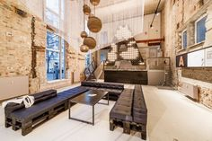 A space: Lofts in Berlin Mitte / plajer & franz studio cardboard suspended spheric lighting,  rustic leather sofa on pallet, metallic table , industrial place with original wall