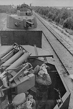 Soviet Armoured train. RED ARMY armoured train in transit. In the foreground two officers on look near the anti-aircraft machine guns, quad-mounted Maxim machine-guns .