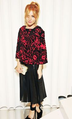 Sienna Miller wears a printed top, pleated skirt, black heels, and a clutch