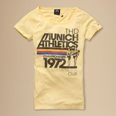 Vintage at its best. Stylish tee with a retro 'Munich Athletics' print on the chest. Scoop neck styling in super soft cotton blend jersey. Tommy Hilfiger flag embroidered on the left sleeve. Comes with a matching tote bag.This style runs true to size.