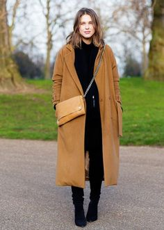 A camel coat is worn over a complete black look: black sweater, skinny jeans and ankle boots