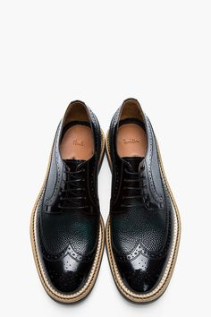 PAUL SMITH // Black and green pebbled leather brogues 32260M049002 Low-top buffed leather longwing brogues in patent black. Brogue detailing throughout. Tonal Derby-style lace-up closure. Pebbled leather accent panels in deep green. White and green running stitches at tan foxing. Rubber sole in grey. Tonal stitching. Upper and lining: leather. Sole: synthetic. Made in Italy. $560 CAD