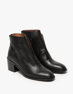 From Jeffrey Campbell, a classic ankle boot in black.  Features zipper back, tongue design, rounded toe, thin stitched detail, textured leather uppers, leather lining, synthetic outsoles and stacked heel.  •	Ankle boot in black •	Zipper back •	Tongue