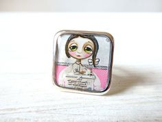 Big square ring. Little child with big eyes, pink.