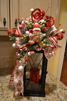 Dress up your lantern with festive gingerbread swag. This swag attaches to your own lantern and does NOT include the lantern pictured. The arrangement is attached to the ribbon and simply ties around the top of the lantern. This swag is attached to a 20 inch lantern but could be used on another size. It measures approx. 11x18. I recommend using a battery operated candle inside the lantern.