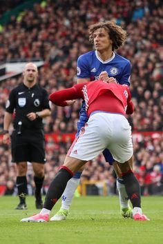 David Luiz of Chelsea tangles with Marcos Rojo of Manchester United during the Premier League match between Manchester United and Chelsea at Old...