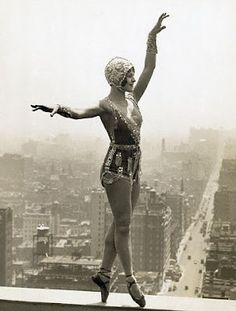 Lina Basquett, well known dancer and musical comedy star, rehearsing new steps for a coming production on a ledge of the roof of the Hotel Commodore twenty eight stories belos is 42nd Street, whose hurrying throngs are unaware of the dancer balanced far above their heads.