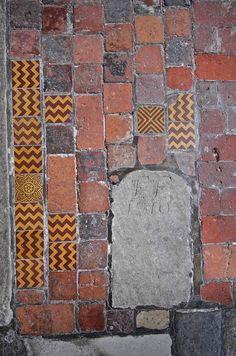 Great floor: bricks, tiles, and tombstone.