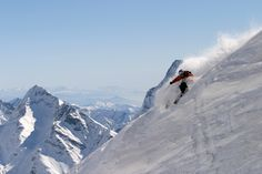 A man skiing freeride off piste backcountry in the Italian ski resort of Champoluc, with stunning snowy mountain peaks and summits behind him.  Champoluc is a delightful, unspoilt village lying at the top of the Ayas Valley, below the imposing Monte Rosa mountain chain with its towering peaks and extensive glaciers.