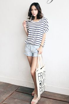 Simple summer outfit with the striped tee, light washed shorts, and white sandals with a graphic tote bag