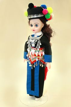 The attire of this doll is from the Hmong of Luang Prabang, Laos. Known as the Hmong Sev Plooj because their aprons are blue with black center panels, they are part of the White Hmong group. The headdress is very distinctive because of the pompoms on the back and the thin black and white siv ceeb wrapped once around it like a headband. She wears a typical money belt, bag, and sash similar to other groups of Hmong in Laos. However the ends of the sash are decorated with a synthetic yarn etc. Hmong People, Luang Prabang, Embroidered Bag, I Give Up, Traditional Fashion, White Skirts, Headdress, Asian Fashion, Everyday Fashion