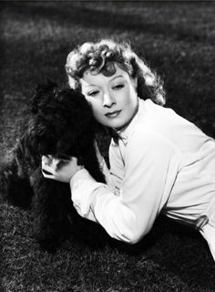 Greer Garson posing with French Poodle, Coco, 1939